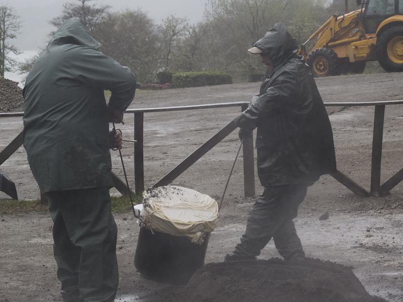 Trabalhadores a tirar panela de cozido das Furnas do buraco