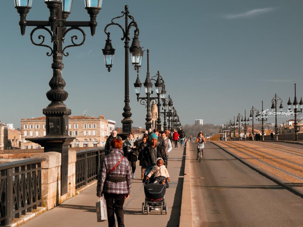 Ponte histórica com candeeiros antigos e muitas pessoas a passar