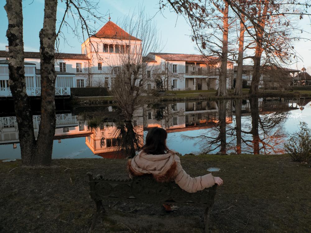 mulher sentada junto ao lago ao pôr do sol em Bordéus