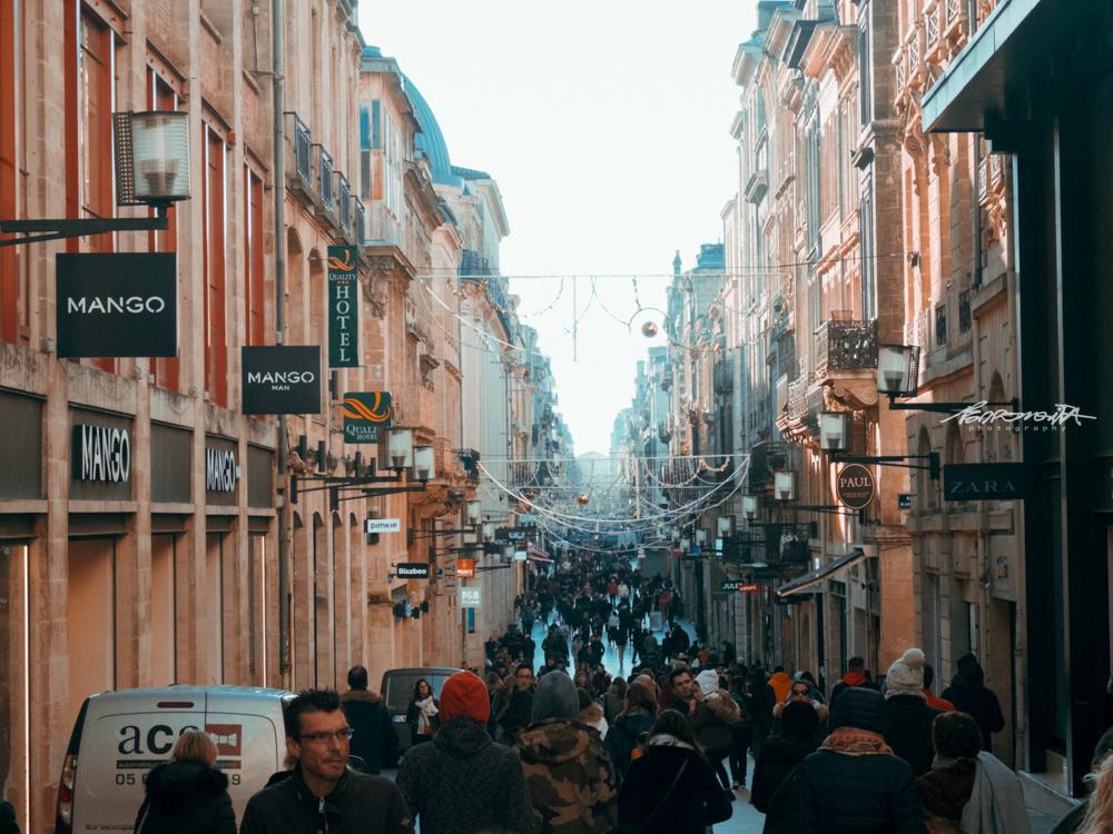 Rua movimentada cheia de lojas e pessoas