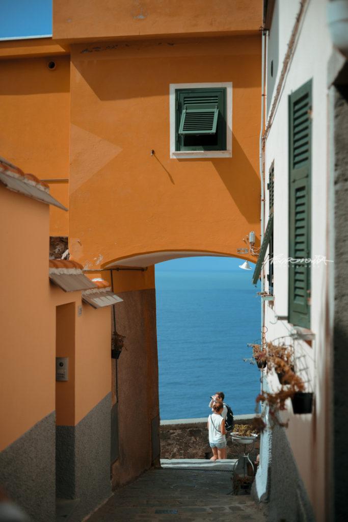 Beco colorido com vista para o mar com turistas