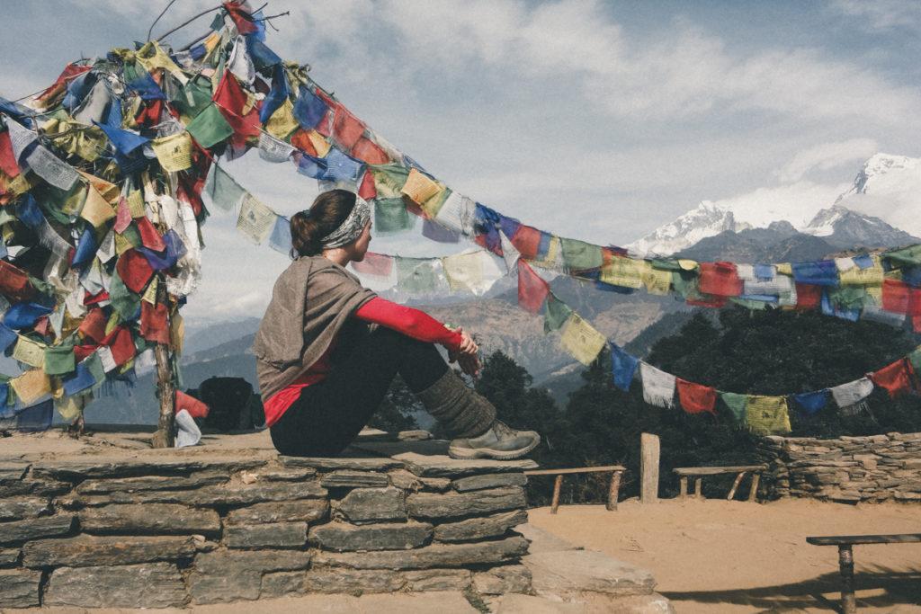 Mulher sentada num muro no Nepal