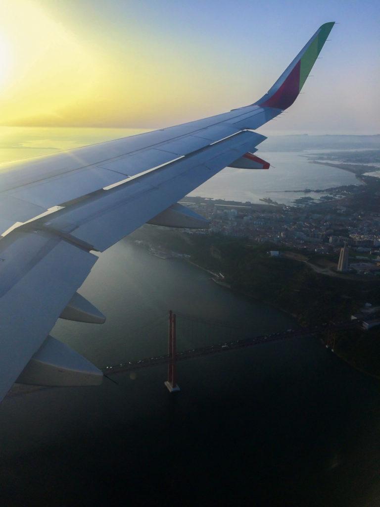 asa de um avião sobre o rio tejo e a ponte 25 de abril
