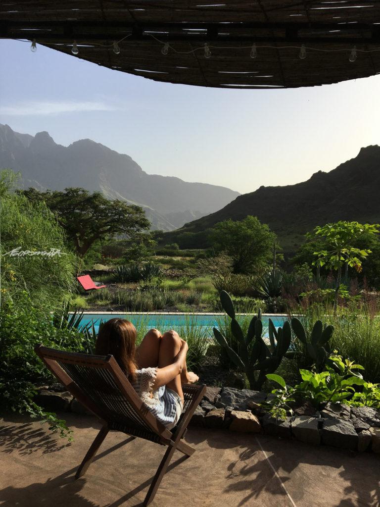 mulher sentada na piscina com vista para as montanhas