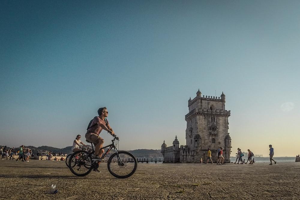 homem de bicicleta na torre de belem