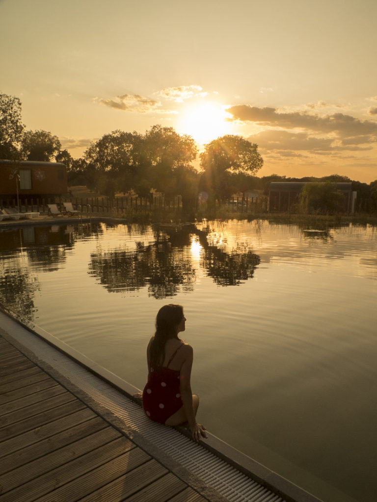 mulher em piscina biológica ao pôr-do-sol. turismo alentejo