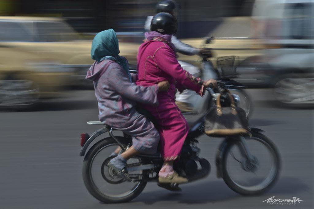 mulheres andam de mota.