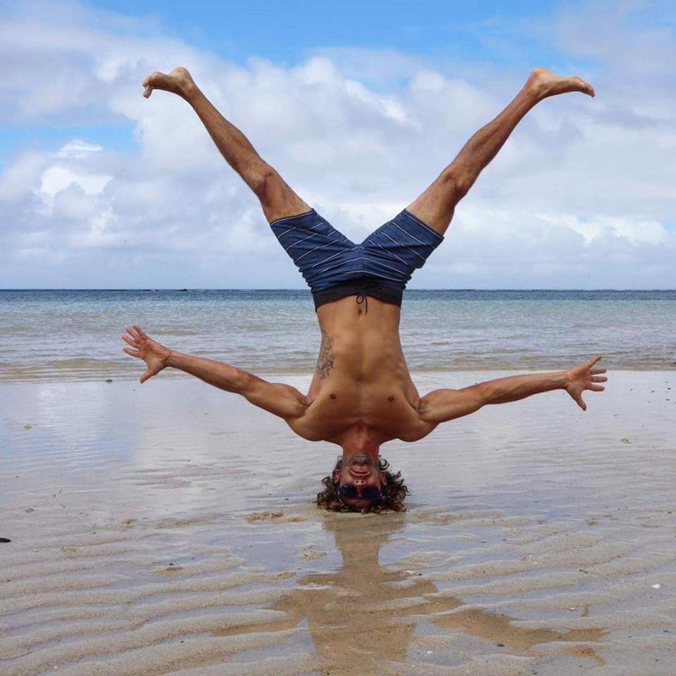 Homem a fazer o pino da praia