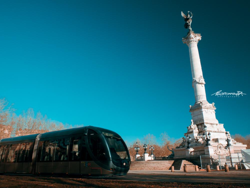Praça histórica com metro a passar