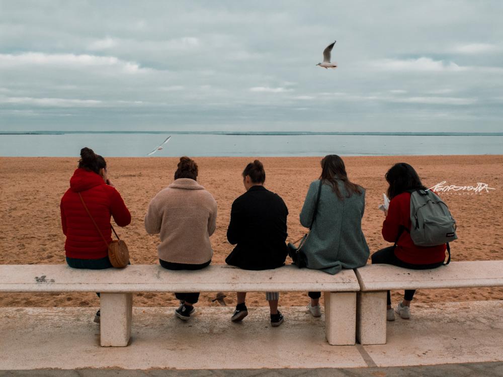 pessoas sentadas a ver o mar