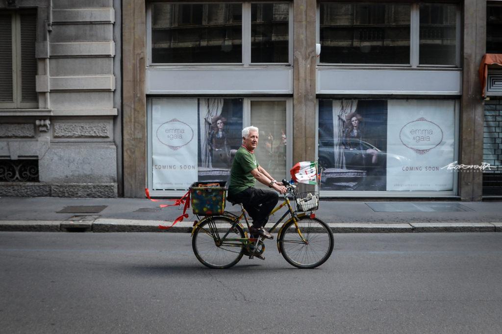 Senhor a andar de bicibleta numa rua de MIlão
