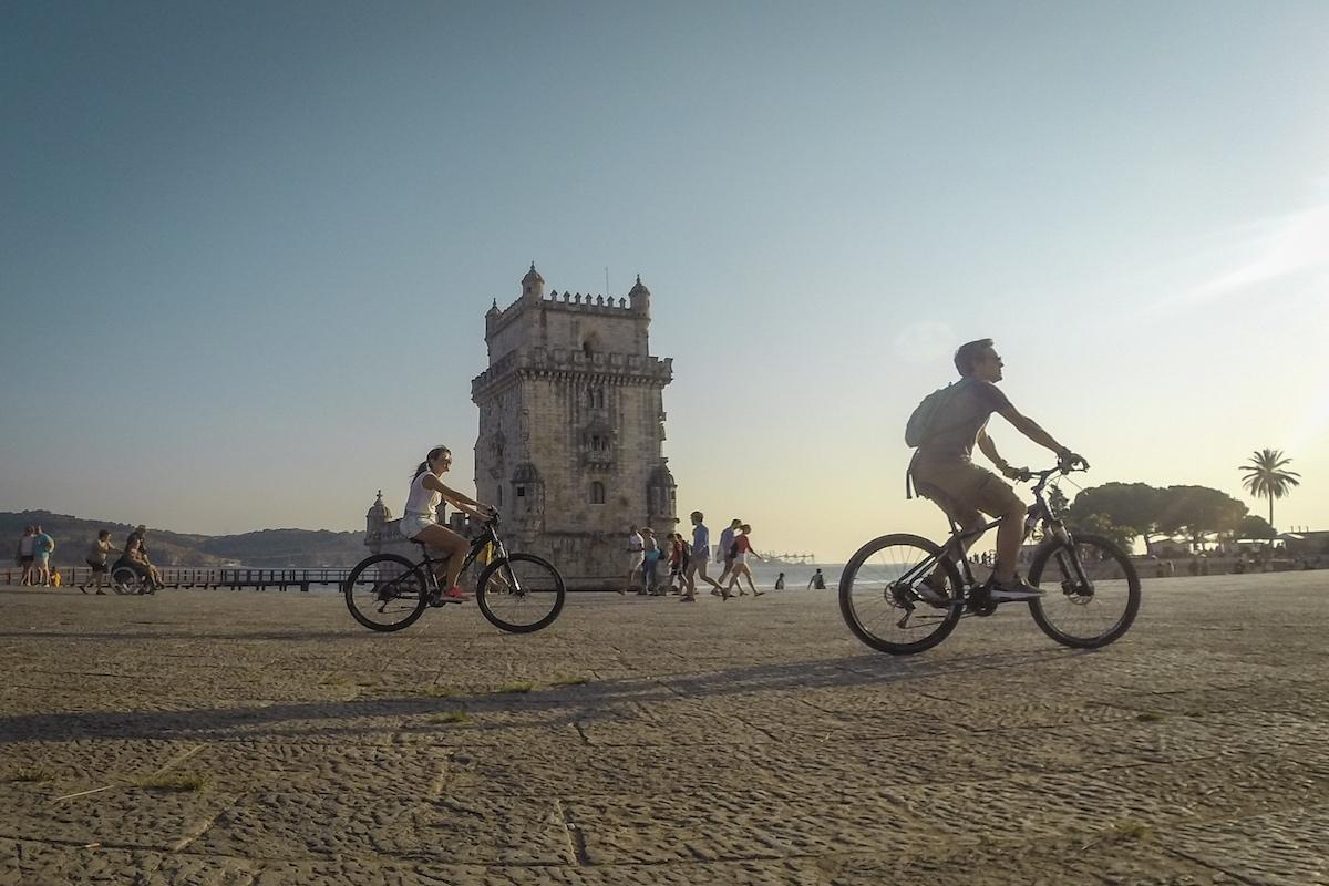homem e mulher de bicileta junto à torre de belém